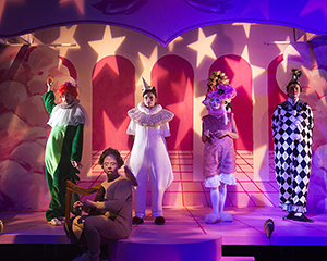 Five actors in costumes on a stage illuminated with starlight